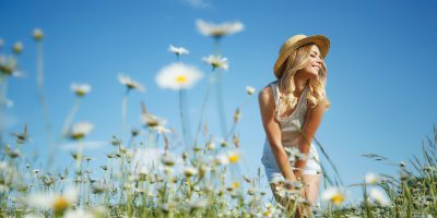 Beautiful woman in the field with flowers.